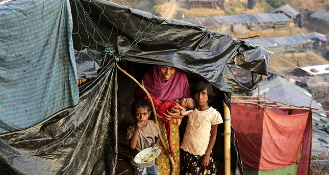 A Rohingya woman poses for a photograph with her children including a new born at her makeshift tent in a camp at Palongkhali, Ukhiya, Coxsbazar, Bangladesh (EPA File Photo)