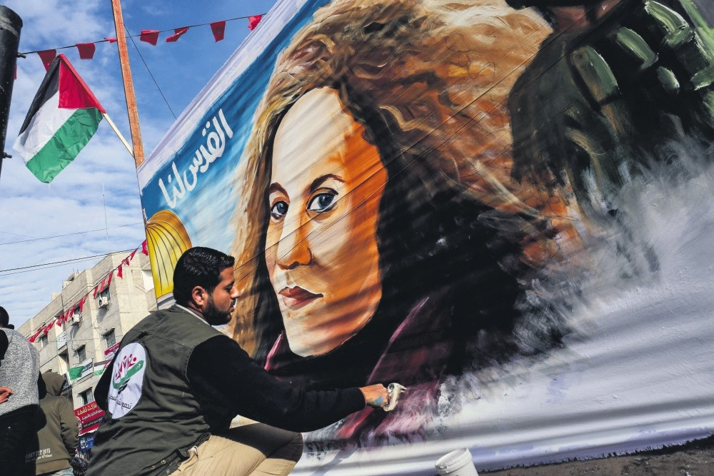 A Palestinian artist paints a portrait of Ahed Tamimi, a 16-year-old prominent campaigner against Israel's occupation and who is currently detained, on a large fabric in Rafah in the southern Gaza Strip.