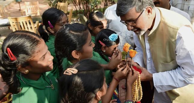 Indian Nobel Peace Prize winner Kailash Satyarthi (R) receiving flowers from schoolchildren.