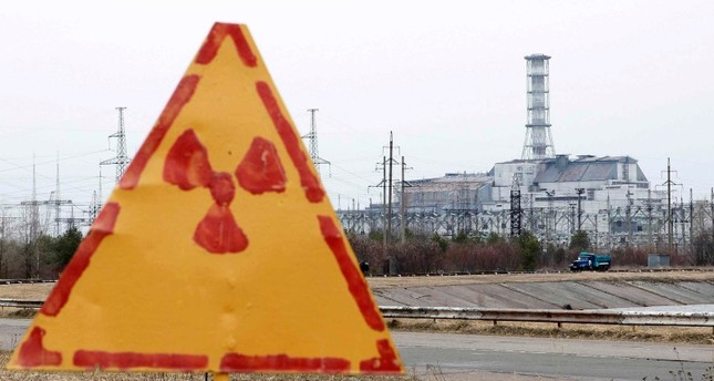 A radiation sign is seen, with a sarcophagus covering the damaged fourth reactor at the Chernobyl nuclear power plant in the background, April 4, 2011. (Reuters Photo)