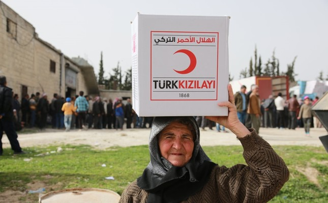 A local resident of Syria's Afrin carries a humanitarian aid package from the Turkish Red Crescent, March 31.