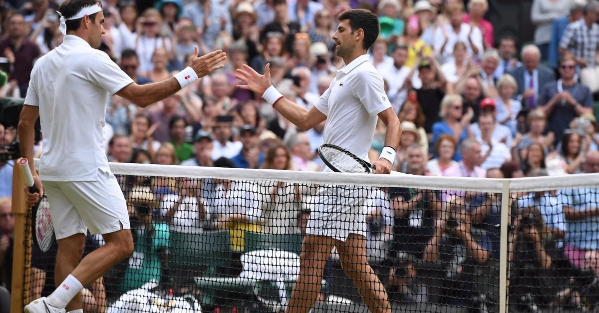 Djokovic shakes hands with Federer after his victory in the menu2019s singles final in Wimbledon, July 14, 2019.