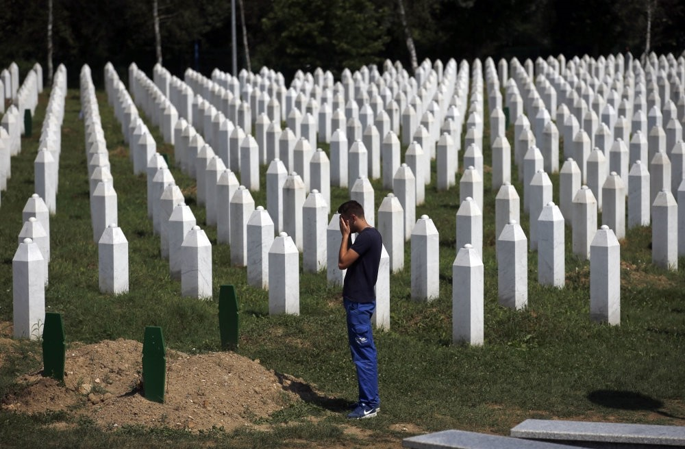 A man prays among gravestones at the memorial center of Potocari near Srebrenica, Bosnia-Herzegovina, Aug. 14, 2018.