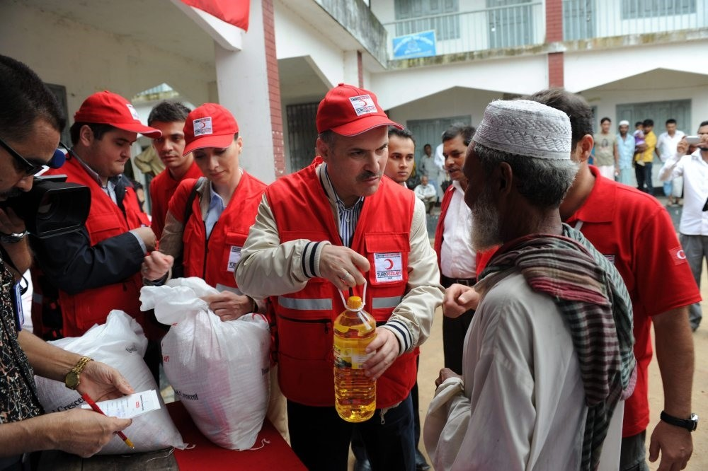 Members of the Turkish Red Crescent distribute aid to Rohingya Muslims living in a refugee camp in the Rakhine state.