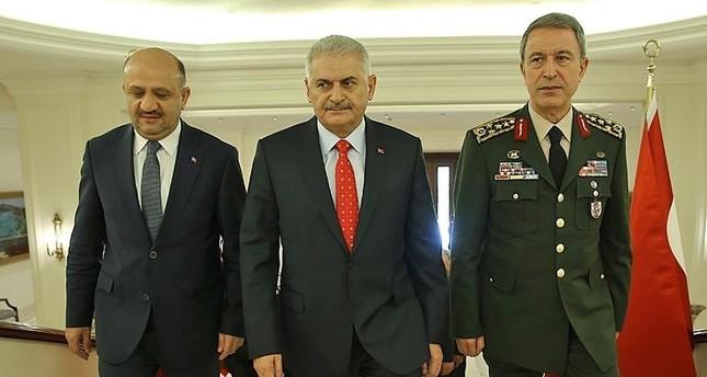 رئيس الوزراء التركي بصحبة وزير الدفاع فكري إيشيق ورئيس الأركان خلوصي آقار (الأناضول)