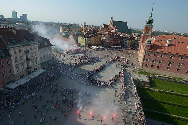 Warsaw residents create a symbol of The Kotwica - a World War II emblem of the Armia Krajowa (Home Army, or AK) - during a ceremony commemorating the 73rd anniversary of the Warsaw Uprising, in the Old Town, Warsaw, Poland, Aug. 01 2017. (EPA Photo)