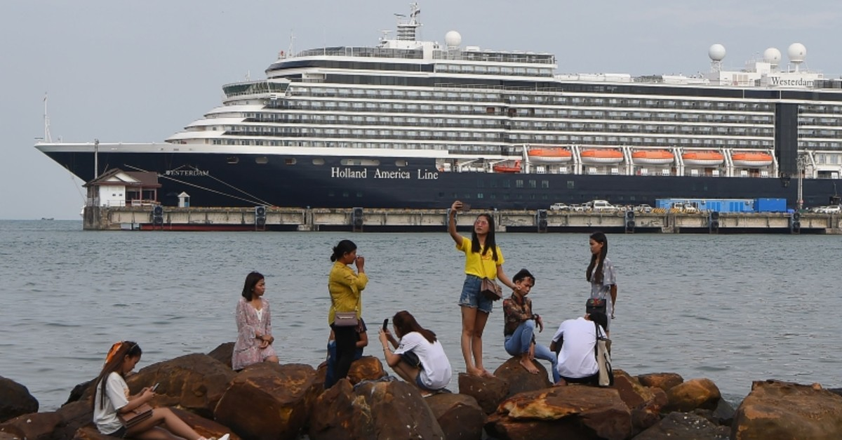 People take pictures on rocks next to the docked Westerdam cruise ship in Sihanoukville on February 18, 2020, as authorities checked if any passengers that remained could have the COVID-19 coronavirus (AFP Photo)