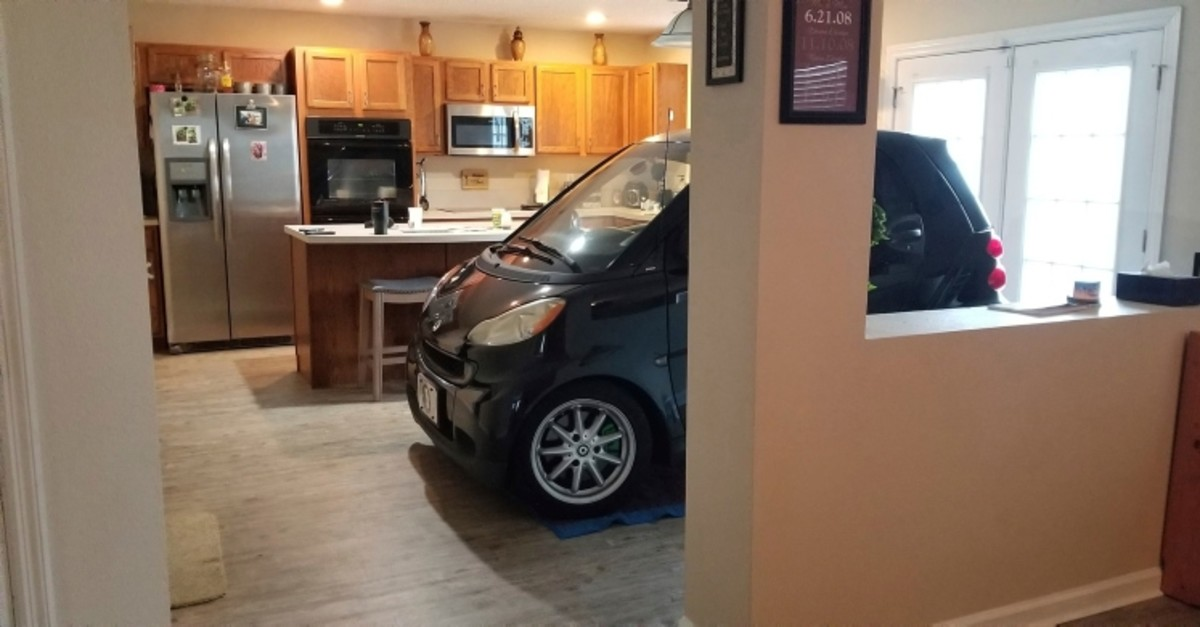 In this Sept. 3, 2019 photo made available by Jessica Eldridge shows her husband's Smart car parked in their kitchen in Jacksonville, Fla. (AP Photo)