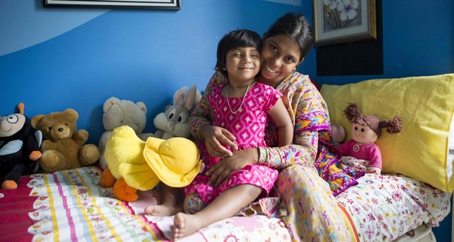 The photo shows three-year-old Choity Khatun (L) with her mother Shima (R) in hospital in Melbourne after she had life saving reconstructive surgery. (AFP Photo)