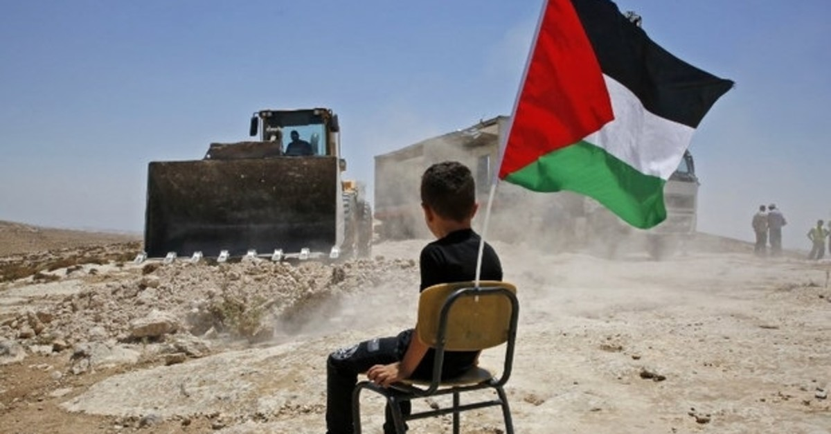 A Palestinian boy watches as Israeli authorities demolish a school site in the south of the West Bank city of Hebron, July 11, 2018.