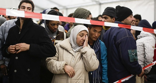 In this file photo taken on Oct. 15, 2015, refugees wait in exclusion zone for transport to a registration office at the State Office of Health and Welfare in Berlin (AP)