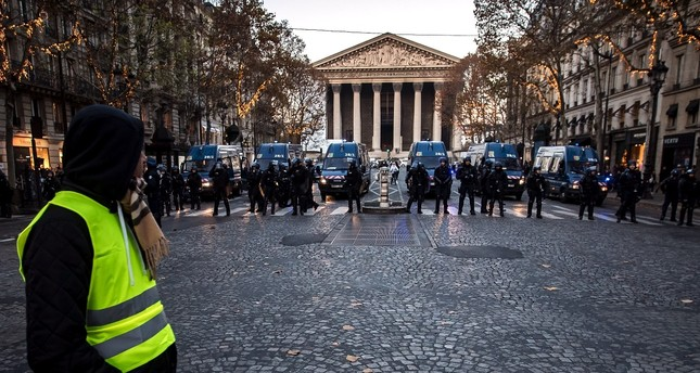 A protesters wearing a yellow vest watches anti-riot police Paris, Nov. 17.