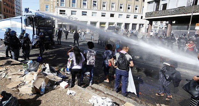 Italian Police use a water cannon as they clash with refugee squatters who had occupied a small square in central Rome, Italy August 24, 2017. (Reuters Photo)
