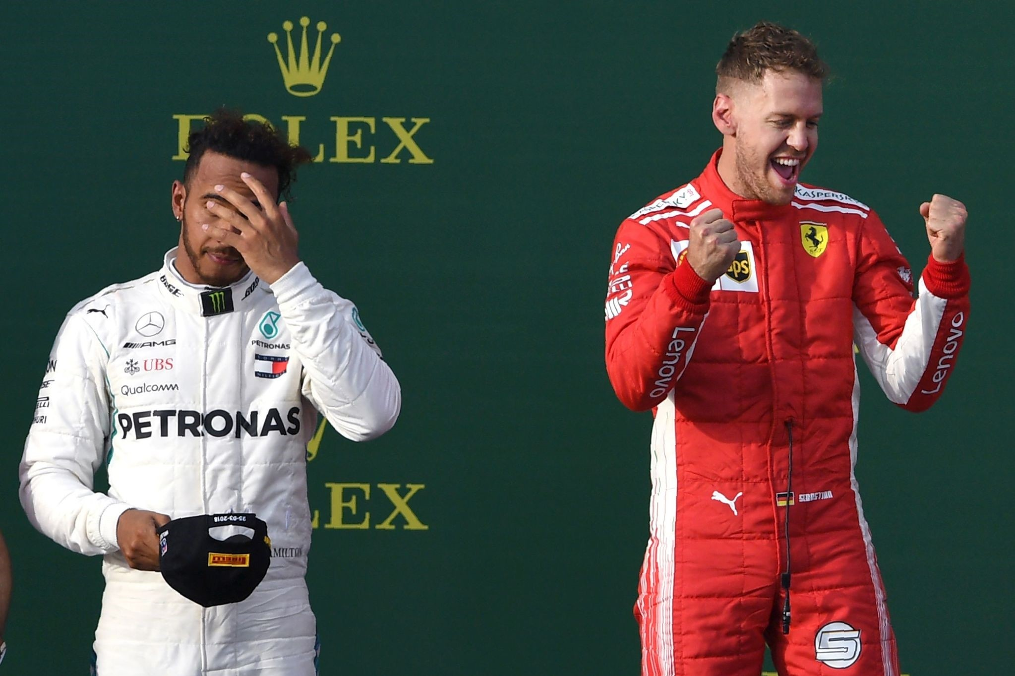 Ferrariu2019s German driver Sebastian Vettel (R) celebrates winning the Formula One Australian Grand Prix beside second-placed Mercedesu2019 British driver Lewis Hamilton (L) in Melbourne.