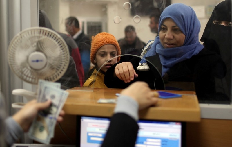 A Palestinian civil servant in the Gaza Strip receives her salary paid by Qatar, in Khan Younis in the southern Gaza Strip, Dec. 7, 2018. (Reuters Photo)