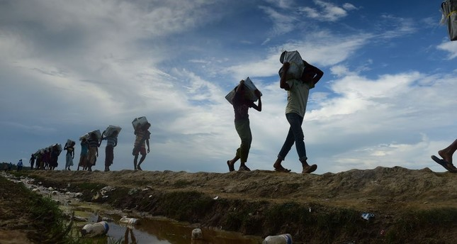 Bangladeshi workers carry relief supplies for Rohingya refugees in the Palongkhali area between Bangladesh and Myanmar, Oct. 18.