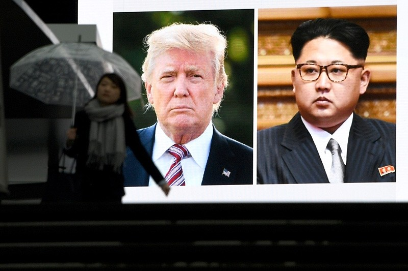 A pedestrian walks in front of a huge screen flashing a news report relating to US President Donald Trump and North Korean leader Kim Jong agreeing to meet for talks in Tokyo on March 9, 2018. (AFP Photo)