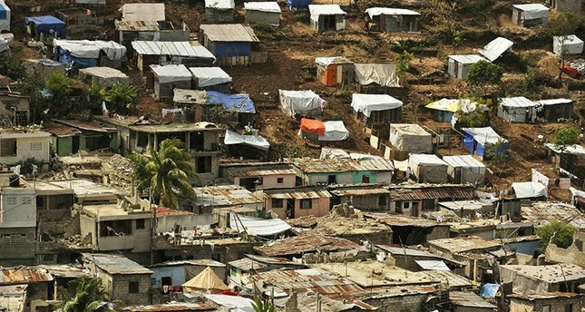 Tents installed by earthquake survivors are seen next to destroyed houses in Port-au-Prince March 20, 2010 (Reuters File Photo)