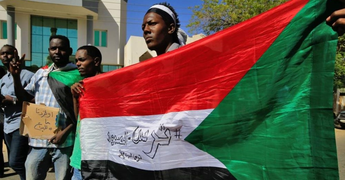 Sudanese demonstrators carry placards and wave their country's national flag as they gather to protest outside the Foreign Ministry, Khartoum, Jan. 28, 2020. (AFP Photo)