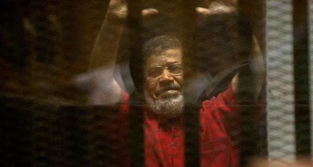 Former Egyptian President Mohammed Morsi raises his hands inside a defendants cage in a makeshift courtroom at the national police academy, in an eastern suburb of Cairo, Egypt, Saturday, June 18, 2016. (AP Photo)