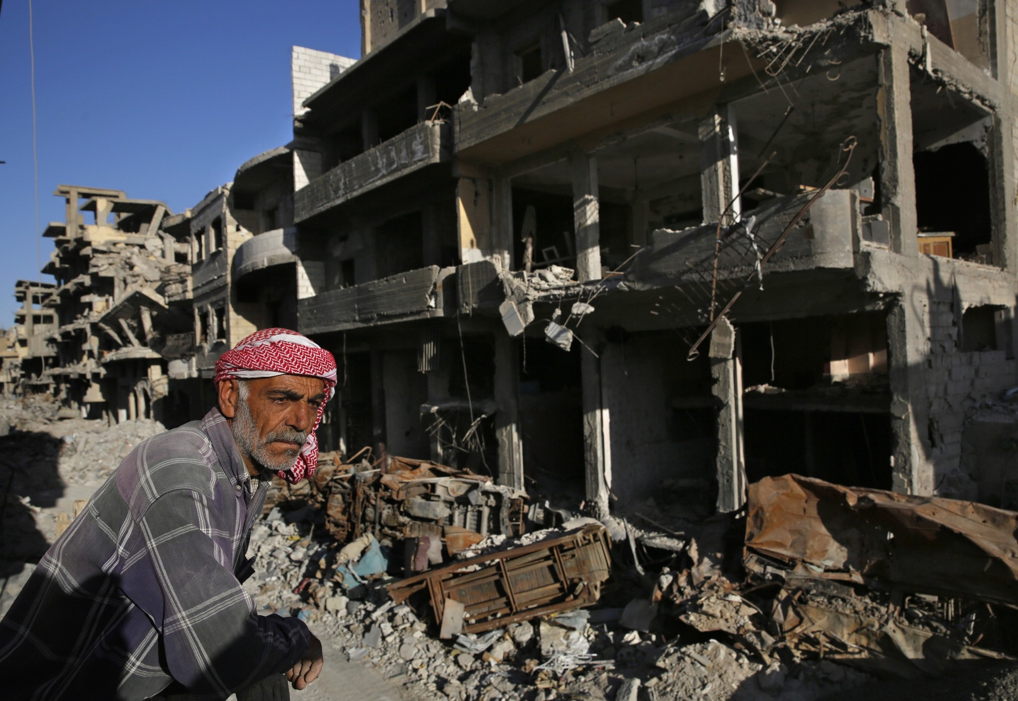 In this Thursday, April 5, 2018 photo, a Syrian man stands between buildings that were damaged last summer during fighting in Raqqa, Syria. (AP Photo)