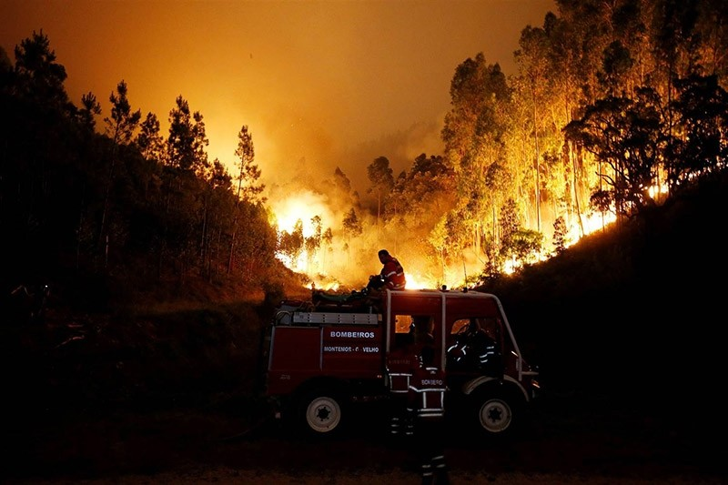 Firefighters work to put out a forest fire near Bouca, in central Portugal. (Reuters Photo)