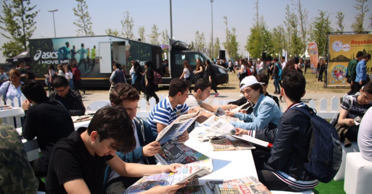 Young men and women reading newspapers on the sidelines of a youth festival in Istanbul in May 2018. The youth make up 15.8 percent of the population in Turkey.