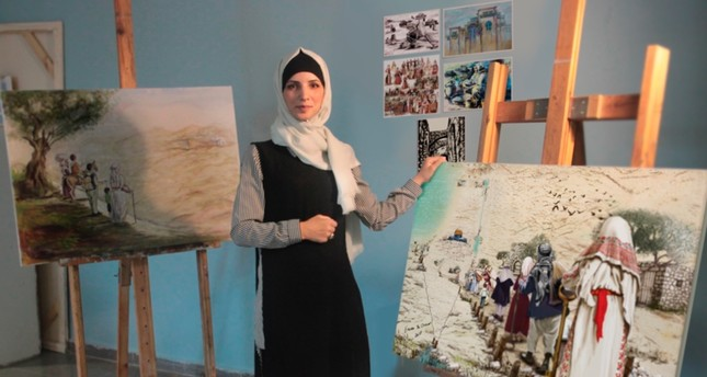 Palestinian artist Iman Abu Arra poses with her paintings in her studio at Hacettepe University in Ankara.