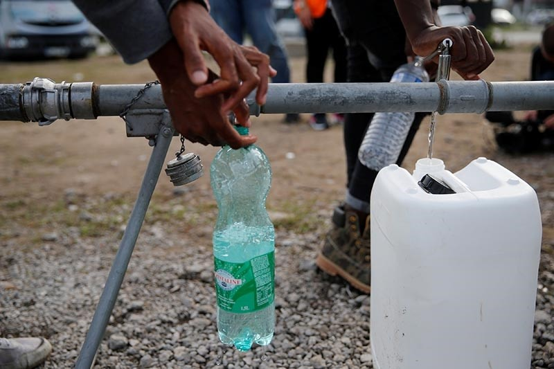 Migrants fill bottles and jerrican at a portable drinking water system near the former ,jungle, in Calais, France, August 23, 2017 (Reuters Photo)