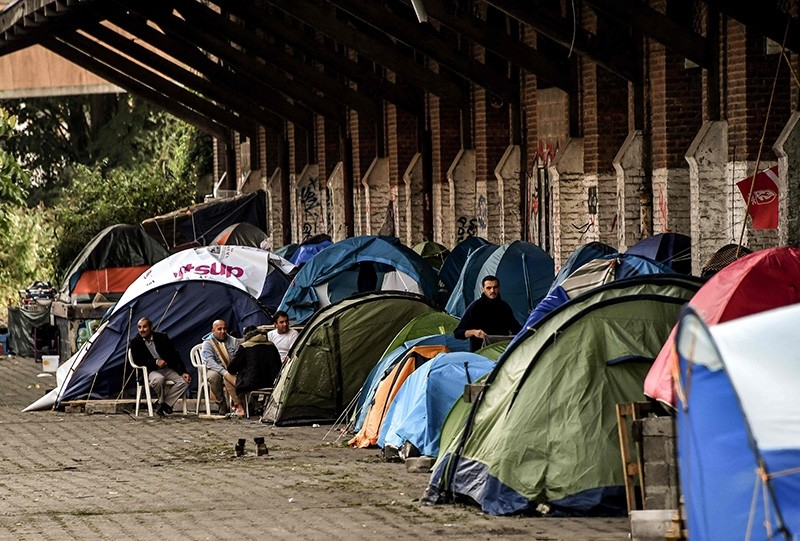 Men sit outside tents on October 6, 2017 in Lille, northern France at a migrants and refugees makeshift camp in the former station of St Sauveur. (AP Photo)