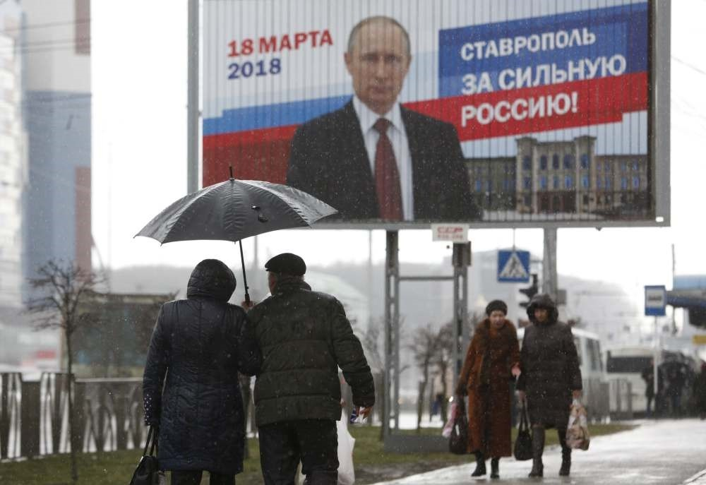 People walk past a campaign poster for Russian President Vladimir Putin, Stavropol, Russia, March 14, 2018. The board reads ,Stavropol is for strong Russia!,
