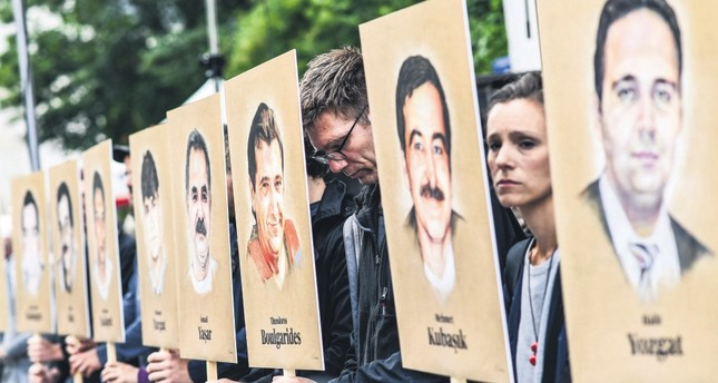 People hold portraits of NSU victims in front of the Higher Regional Court in Munich, Bavaria, Germany, July 10 .