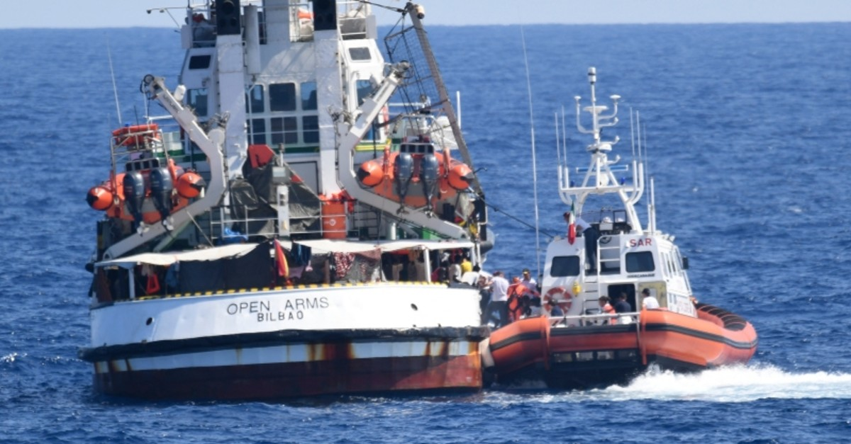An Italian Coast Guard boat, right, approaches the Spanish humanitarian rescue ship Open Arms, off the Sicilian island of Lampedusa, southern Italy, Tuesday, Aug. 20, 2019. (AP Photo)