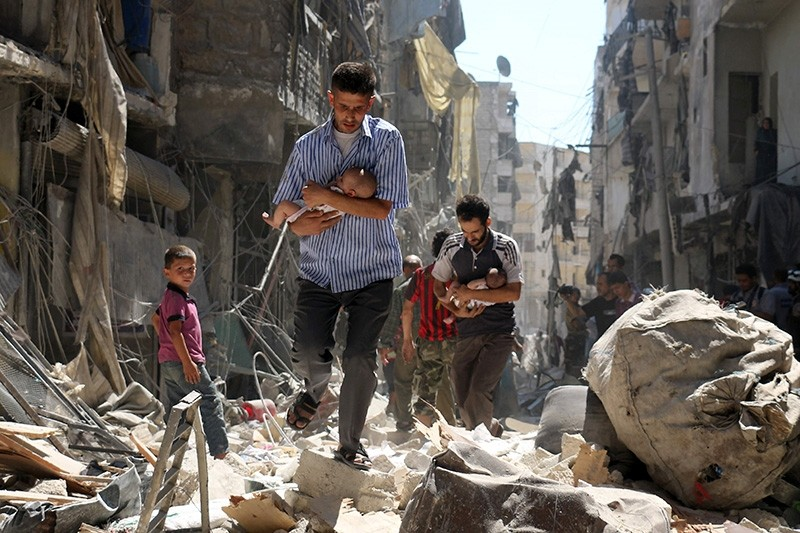 Syrian men carrying babies make their way through the rubble of destroyed buildings following a reported air strike on the oppositionl-held Salihin neighbourhood of the northern city of Aleppo (AFP File Photo)