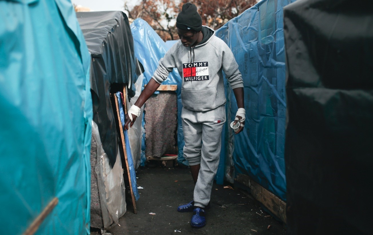A sub-Saharan migrant from Senegal walks outside the tent where he lives at at Oulad Ziane camp, Casablanca, Dec. 6.