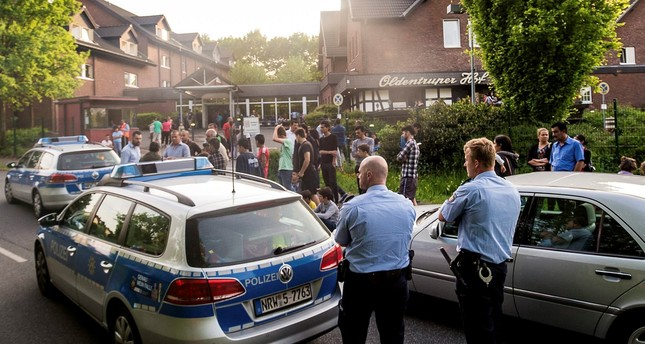 police and refugees stand near a refugee shelter in Bielefeld, Germany. (AP Photo)
