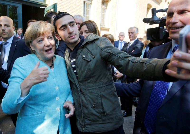 A migrant takes a selfie with German Chancellor Angela Merkel outside a refugee camp near the Federal Office for Migration and Refugees after registration at Berlin's Spandau district, Germany, September 10, 2015. (Reuters Photo)