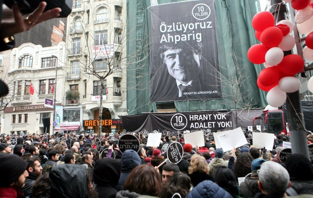 A crowd commemorating Hrant Dink gathered on Jan. 19, 2017, outside Agos weekly, against the backdrop of a poster of the late journalist.