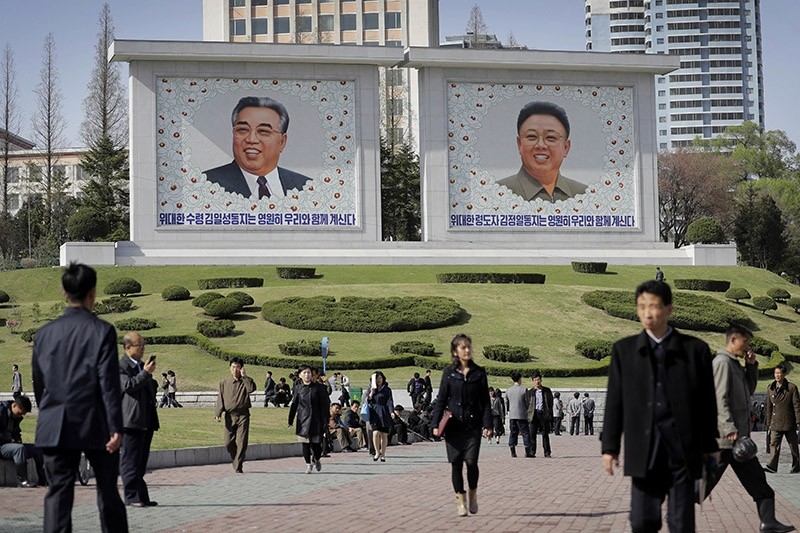 North Koreans walk along downtown Pyongyang where portraits of the late leaders, Kim Il Sung, left, and Kim Jong Un, are seen in the background Tuesday, April 18, 2017. AP Photo.