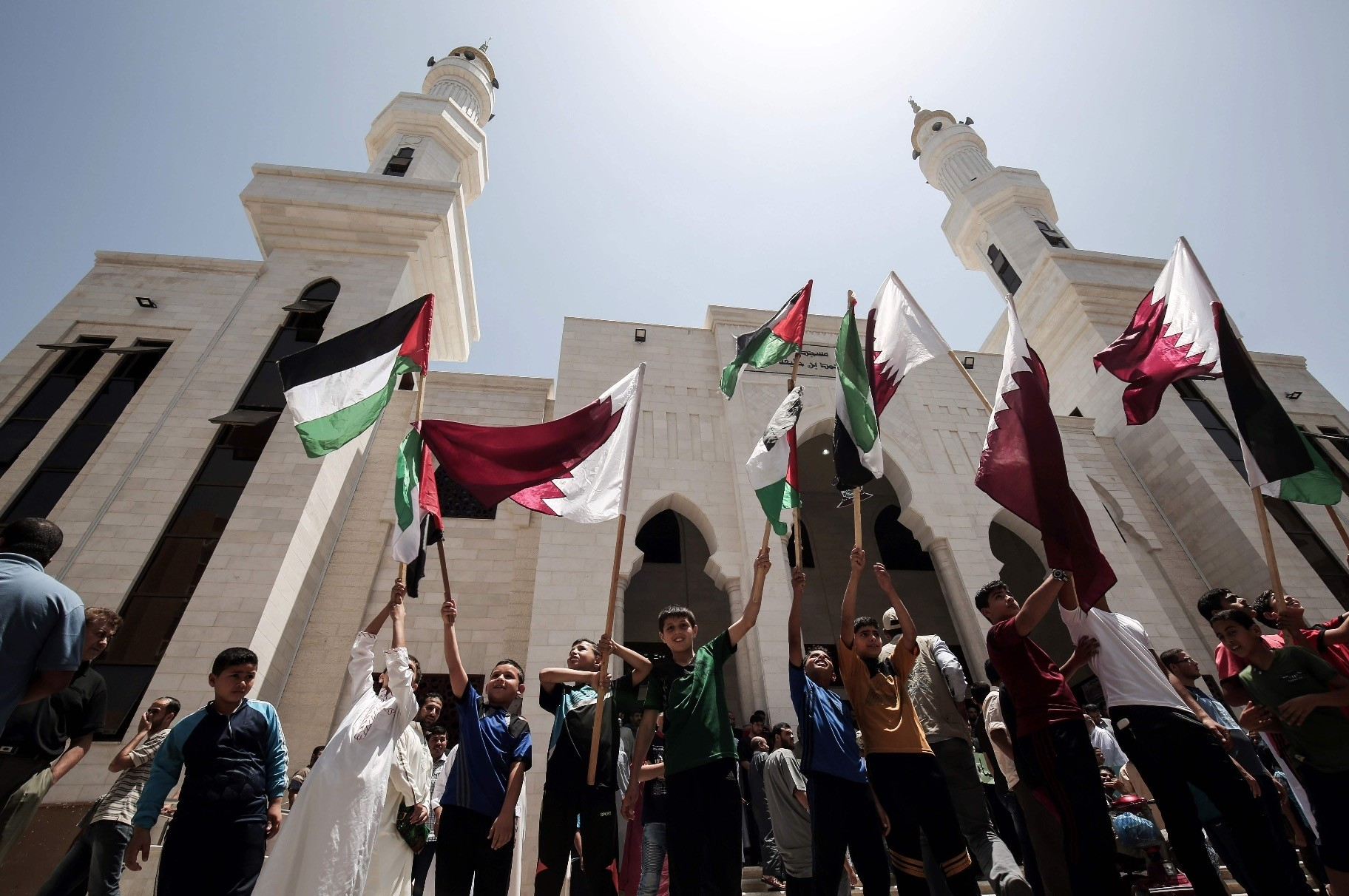 Palestinians attending a rally in support of Qatar after the blockade by the Gulf countries, led by Saudi Arabia and the UAE, were implemented against it, at the Qatari-funded housing project in the southern Gaza Strip city of Khan Yunis on June 9.