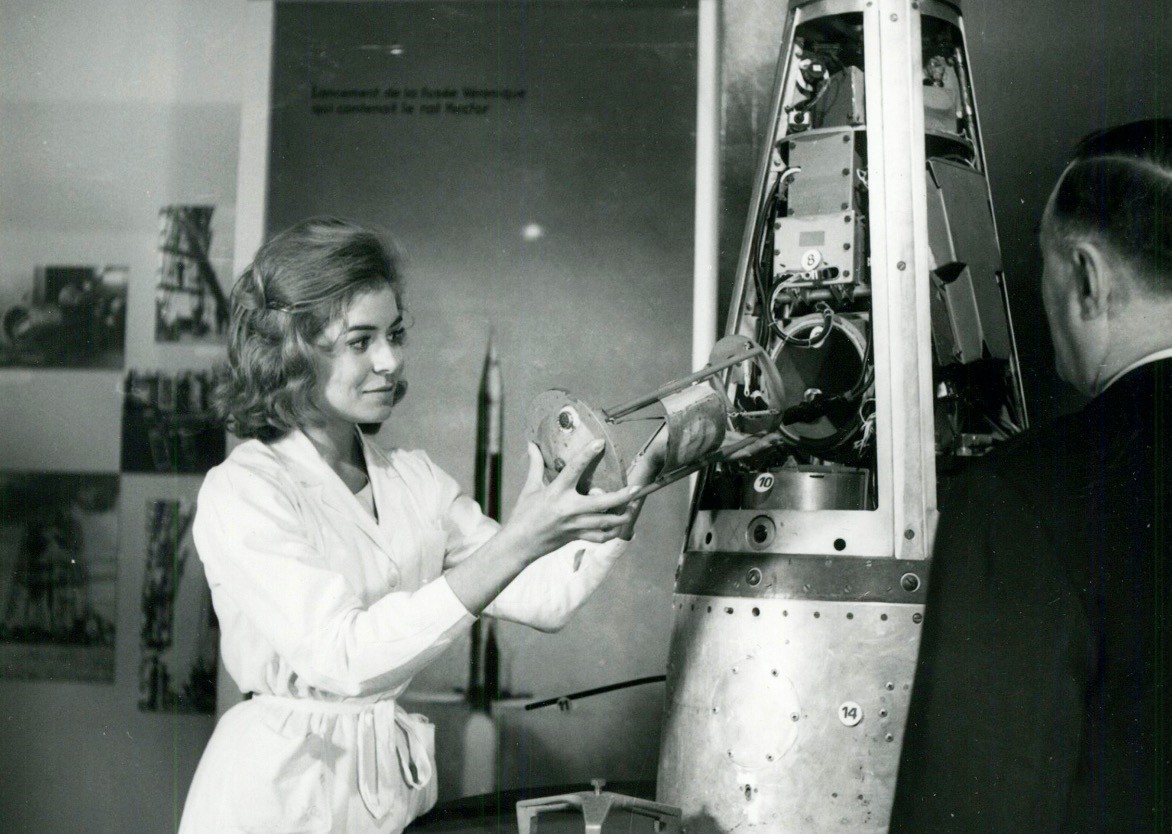 A woman places the rat Hector, first French Spatial traveler, into French rocket Veronique.