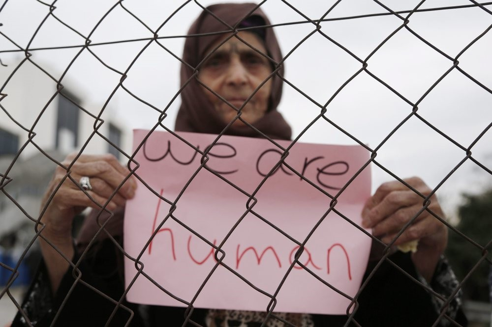 A refugee woman holds a placard during a protest demanding better living conditions at a makeshift refugee camp inside a former airport in Athens on Feb.5.