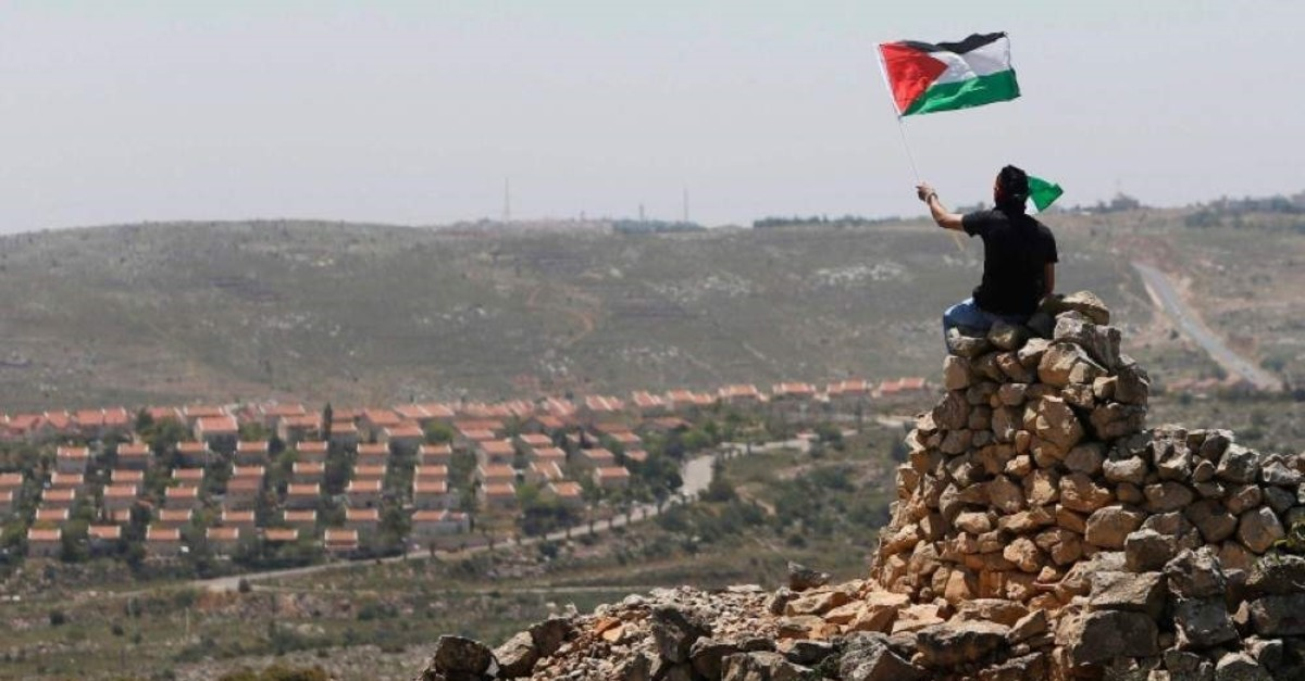 A protester waves a Palestinian flag in front of the Jewish settlement of Ofra during clashes near the West Bank village of Deir Jarir near Ramallah April 26, 2013. (Reuters Photo)