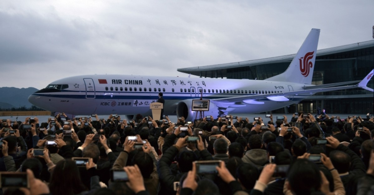 In this Dec. 15, 2018, photo, invited guests take photos of the Boeing 737 Max 8 airplane deliver to Air China during a ceremony at Boeing Zhoushan 737 Completion and Delivery Center in Zhoushan, east China's Zhejiang Province. (AP Photo)