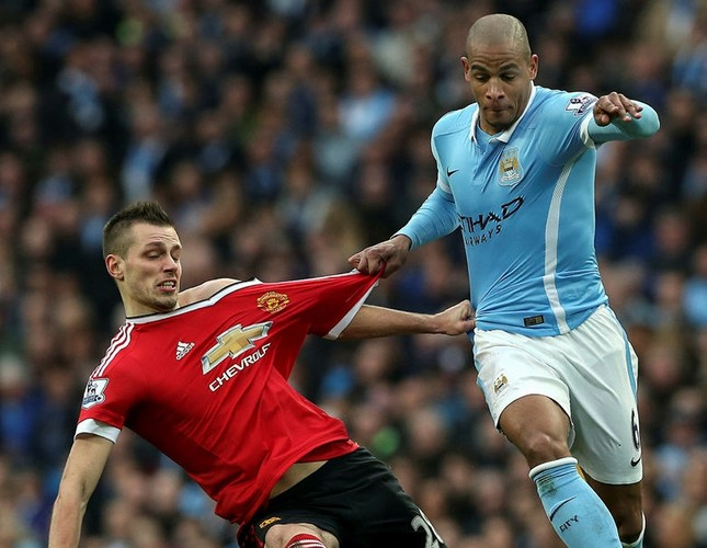 Manchester City's Fernando Reges (R) fights for the ball with Manchester United's Morgan Schneiderlin (L) during the English Premier League soccer match between Manchester City and Manchester United in Manchester, Britain, 20 March 2016.  (EPA Photo)