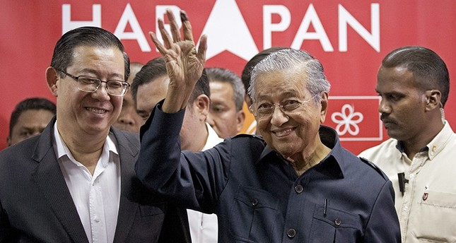Malaysia's Prime Minister Mahathir Mohamad, center, waves next to newly appointed Finance Minister Lim Guan Eng, left, after a press conference to announce his cabinet members in Petaling Jaya, Malaysia, Saturday, May 12, 2018. (AP Photo)