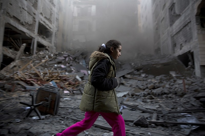 A Palestinian girl walks next to a destroyed residential building hit by Israeli airstrikes in Gaza City, Tuesday, Nov. 13, 2018. (AP Photo)