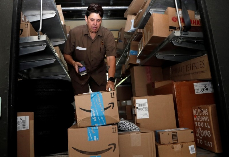 United Parcel Service employee Liz Perez scans an Amazon Prime package for delivery in Miami, Tuesday, July 17, 2018. (AP Photo)