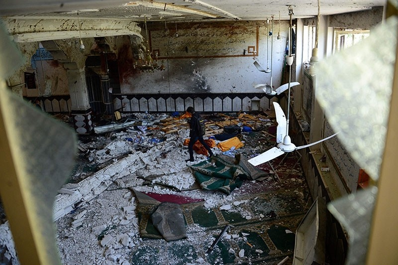 An Afghan media personnel walks through a Shiite mosque after it was attacked by suicide bombers in Herat on Aug. 2, 2017. (AFP Photo)