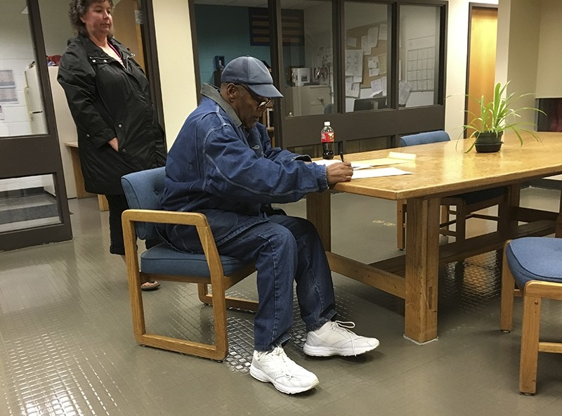 Former football legend O.J. Simpson signs documents at the Lovelock Correctional Center, Saturday, Sept. 30, 2017, in Lovelock, Nev. (AP Photo)